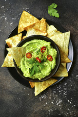 Avocado dip guacamole with tortilla chips.Top view with copy space.