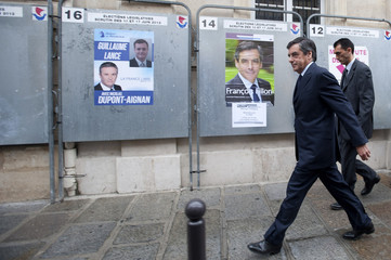 Former French prime minister Fillon and a UMP party candidate for the parliamentary elections leaves a polling station in Paris