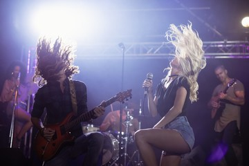 Female singer and male guitarist with tousled hair