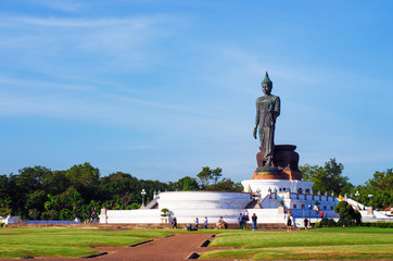 buddha statue outstanding on concrete base with blue sky in buddhism park Thailand.