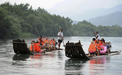 Tourists wearing life jackets sit on rafts in Yongjia County, Zhejiang Province