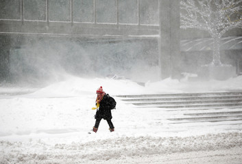 A woman walks through snow in a winter storm in Toronto