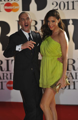 Johnny Vaughan and Lisa Snowdon pose for photographers at the BRIT music awards at the O2 Arena in London