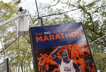 A worker is seen in a bucket truck in front of a sign for the New York City Marathon in the aftermath of Hurricane Sandy in New York