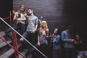 Young friends using mobile phone at nightclub staircase