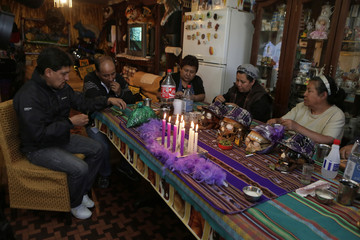 """Devotees attend a ceremony at their home before the """"Dia de los natitas"""" (Day of the Skull) celebrations at the General Cemetery of La Paz"""