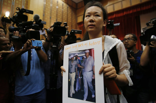 The wife of a passenger aboard the missing Malaysia Airlines Flight MH370, holds a picture of her husband, at a news conference in Putrajaya