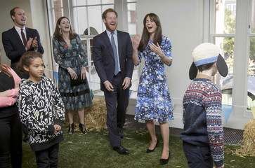 Britain's Prince William (L), Prince Harry, and Kate, Duchess of Cambridge, smile as they take part in 'welly wanging', with children and representatives from charities and Aardman Animations, at the British Academy of Film and Television Arts in London