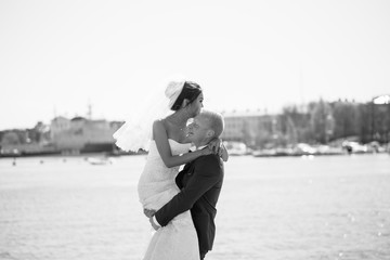 Beautiful asian bride and manful european groom walking on old town near the sea. Wedding concept for your design or magazine