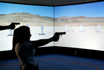 An Arab Israeli police recruit takes aim with her gun towards a screen displaying targets during a training exercise at Israeli police academy center in Beit Shemesh, Israel
