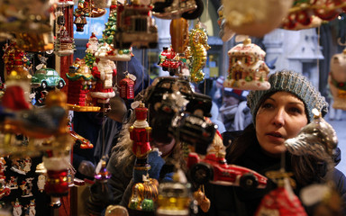A woman looks at Christmas tree ornaments during the Christmas market in Munich