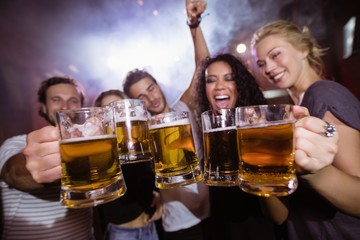 Cheerful friends holding beer mugs together