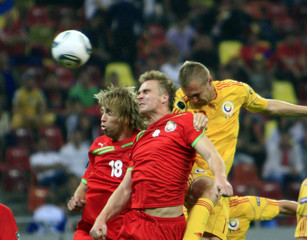 Verkhovtsov and Kornilenko of Belarus challenge Gabriel Tamas of Romania during their Euro 2012 Group D qualifying  soccer match in Bucharest