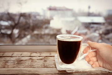 Human hand taking cup of hot coffee from wooden window sill