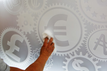 A man cleans a board with different currency signs at a currency exchange office in Madrid