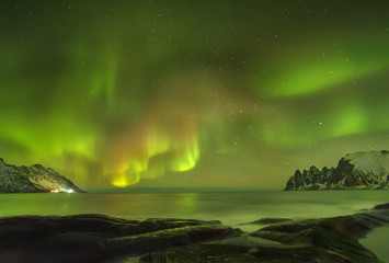 Aurora borealis (Polar lights). View to Steinfjord on Senja island (Oksan on background). Lofoten islands, Norway
