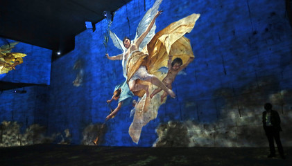 "A visitor looks at a sound and light show as part of the exhibition 'Klimt and Vienna, a century of gold and colors', which projected on the walls of the ""Carrieres de Lumieres"" site (Quarries of lights) in Les Baux-de-Provence"