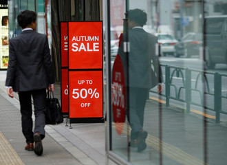 Man walks past a fashion boutique in a shopping district in Tokyo