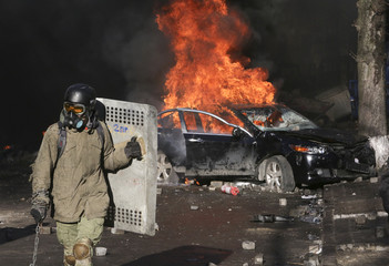 A protester holds a makeshift shield in front of a burning car during clashes with police in Kiev