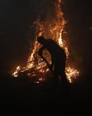 "A man prepares a bonfire during the ""Luminarias"" annual religious celebration in the village of San Bartolome de los Pinares"
