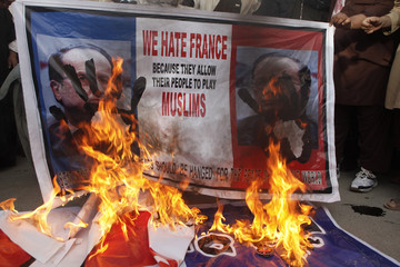People burn posters during a protest against Charlie Hebdo, which featured a cartoon of the Prophet Mohammad as the cover of its first edition since an attack by Islamist gunmen, in Quetta