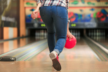 Young woman throwing ball in bowling club