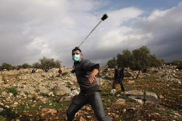 Palestinian protester uses sling to throw stones at Israeli security forces during clashes at protest against controversial Israeli barrier in West Bank village of Bilin