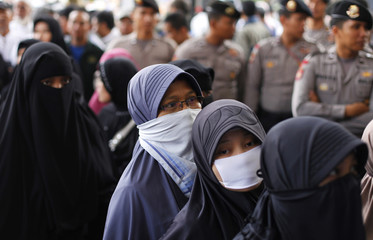Supporters of Indonesian militant cleric Bashir wait during his trial as they are flanked by police standing guard outside a courtroom in south Jakarta