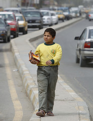 A boy sells chewing gum on a road in Baghdad