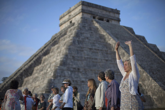 A tourist raises her hands during a group meditation at sunrise near the pyramid of Kukulkan at the archaeological zone of Chichen Itza in Yucatan State