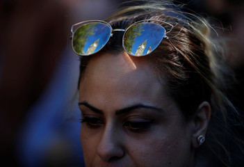 Manchester town hall is reflected in the sunglasses of a woman taking part in a vigil for the victims of an attack on concert goers at Manchester Arena, in central Manchester