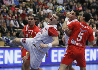 Akizu of Spain attempts to score past Gharbi of Tunisia during their Group A match at the Men's Handball World Championship in Lund
