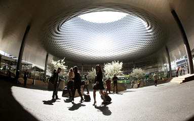 People walk through the newly designed fairground during the Baselworld fair in Basel