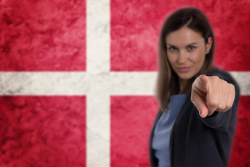 Beautiful businesswoman pointing her finger at you Danish flag background.