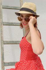 Happy smiling girl wearing straw hat and sunglasses