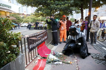 Man wearing Darth Vader costume places flowers at the scene of Thursday's gun and bomb attack, in front of a Starbuck cafe in Jakarta