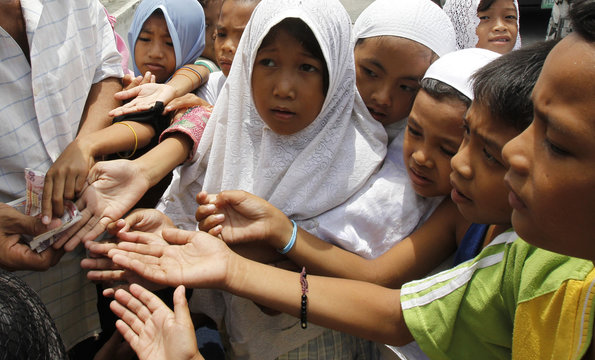 A Filipino Muslim man gives money to Filipino Muslim children after Friday prayers at the Blue Mosque during Ramadan in Taguig, Metro Manila