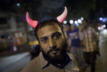 Rehman wears a pair of illuminated devil's horns as he waits for customers to buy his toys outside a fair in Mumbai