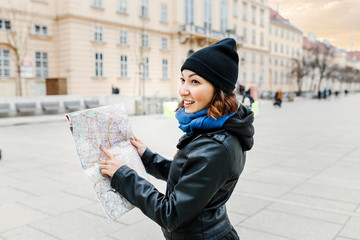 Happy woman in casual is guided by a map in the center of a Vienna city, the concept of travel