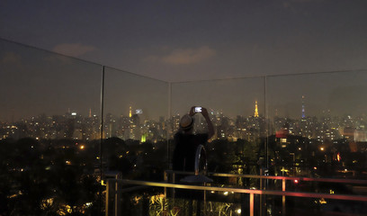 Man takes a picture with his mobile phone of Sao Paulo city from the Skye Bar on the roof of Hotel Unique, in Sao Paulo