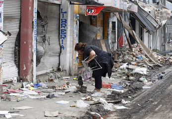 An earthquake survivor searches for salvageable items on a street filled with debris from a massive earthquake in Talcahuano