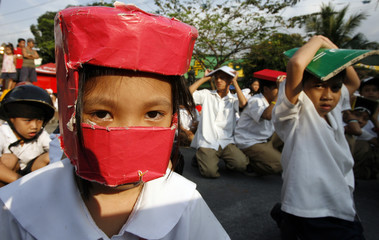 Students use make shift protective head gear and books to cover their heads during an earthquake drill at San Juan elementary school in San Juan