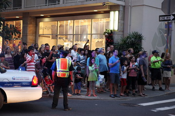 A crowd gathers in Waikiki to watch U.S. President Barack Obama and First Lady Michelle Obama's motorcade as it pulls up at Orchid restaurant (not in the picture) during their Christmas holiday vacation in Honolulu