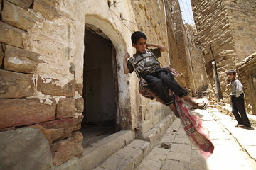 A boy plays on a swing on the gate of his house in the historic city of Thula in Yemen's northwestern province of Amran