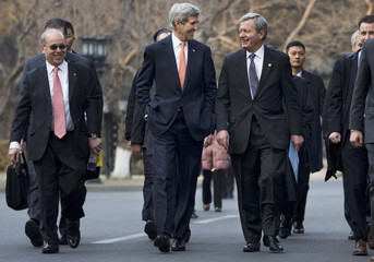 U.S. Secretary of State John Kerry smiles as he walks with U.S. Ambassador to China Max Baucus as they walk to a meeting with Chinese State Councilor Yang Jiechi in Beijing
