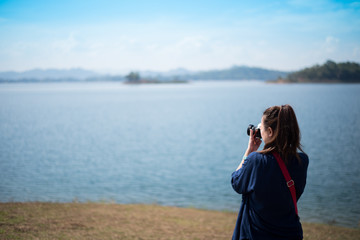 A woman is taking a beautiful landscape photo