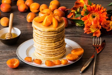 Stack of homemade american pancakes served with honey and apricots on wooden background