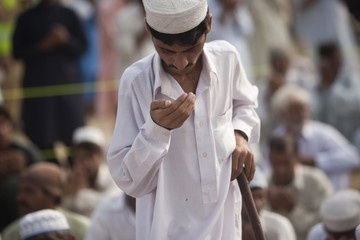 A flood victim prays during an Eid al-Fitr outdoor mass prayer ceremony near a relief camp in Nowshera, Pakistan's northwest Khyber-Pakhtunkhwa Province