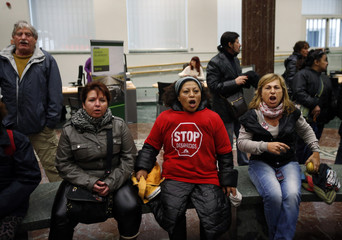 An employee works at her desk as members of the Mortgage Victims' Platform stage a sit-in protest inside a branch of nationalized lender Bankia in Madrid