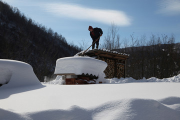 A man shovels snow off from a roof at around minus 26 degrees Celsius (minus 14.8 degrees Fahrenheit) in the village of Jezerc